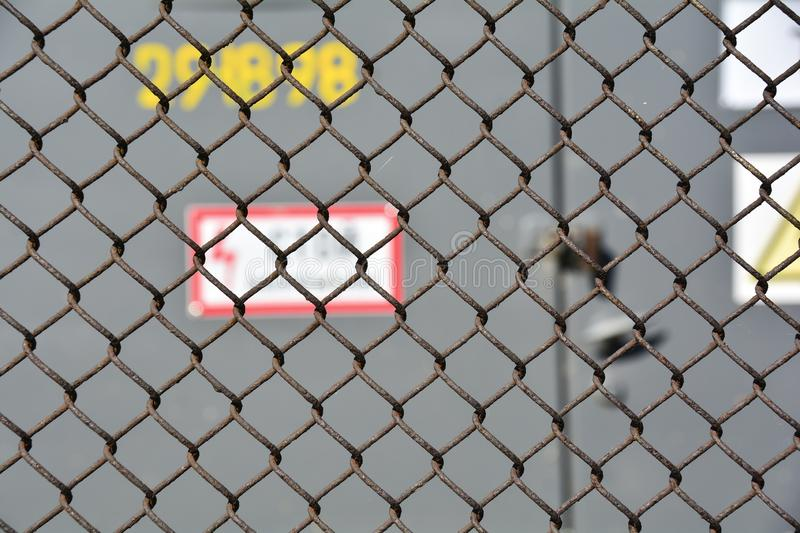 The danger of high voltage. steel mesh fence high-voltage transformer substation outside. Soft focus. Abstract background for royalty free stock image
