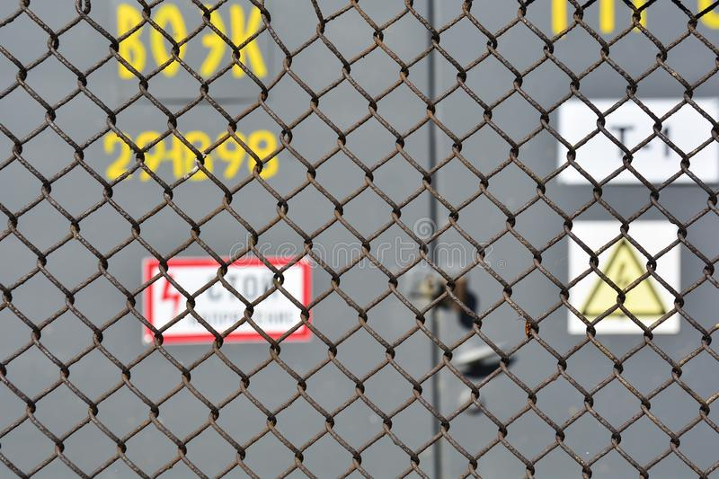 The danger of high voltage. steel mesh fence high-voltage transformer substation outside. Soft focus. Abstract background for stock image