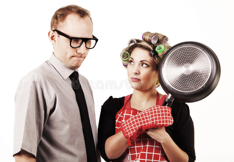 Danger housewife with pan. Serious talking. Danger housewife with pan and accused husband stock photo