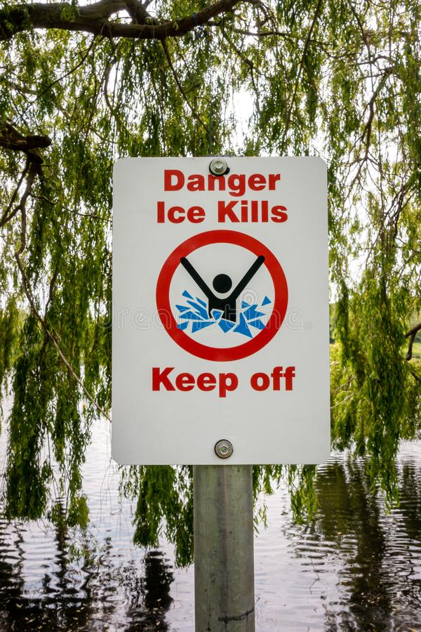 Danger ice kills keep off sign. Post on the bank of a small lake royalty free stock image