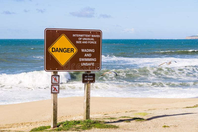 `Danger intermittent waves of unusual size and force` sign, California royalty free stock images