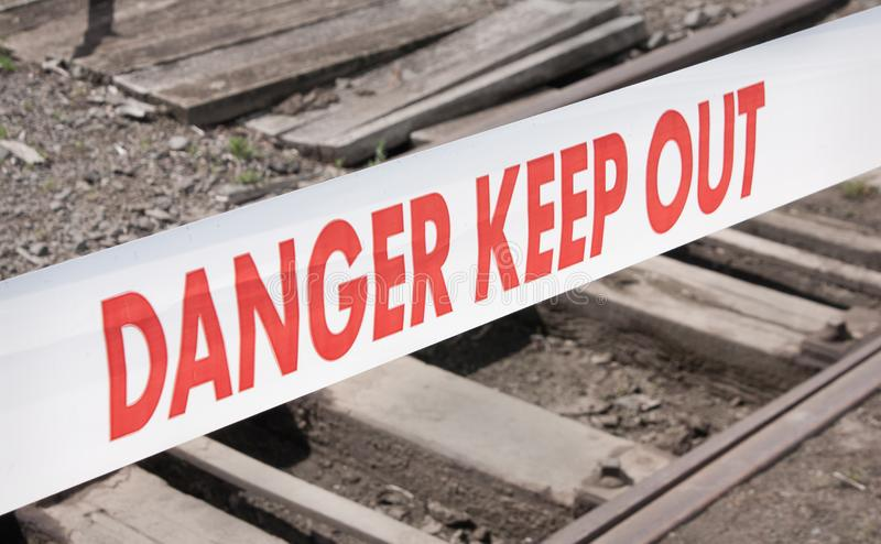DANGER KEEP OUT tape. With railway tracks behind stock photos