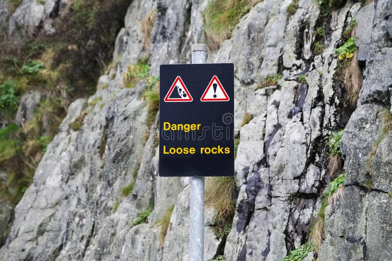 Danger loose rocks steep cliff boulders caution sign for climbing. Uk stock photo