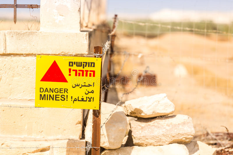Danger Mines! Warning sign and barbed wire. royalty free stock image