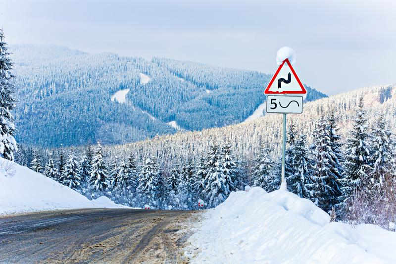 Danger in mountains concept. Slippery roads in hilly area. Snowy landscape. Danger in the mountains concept. Slippery roads in hilly area. Snowy landscape stock photography