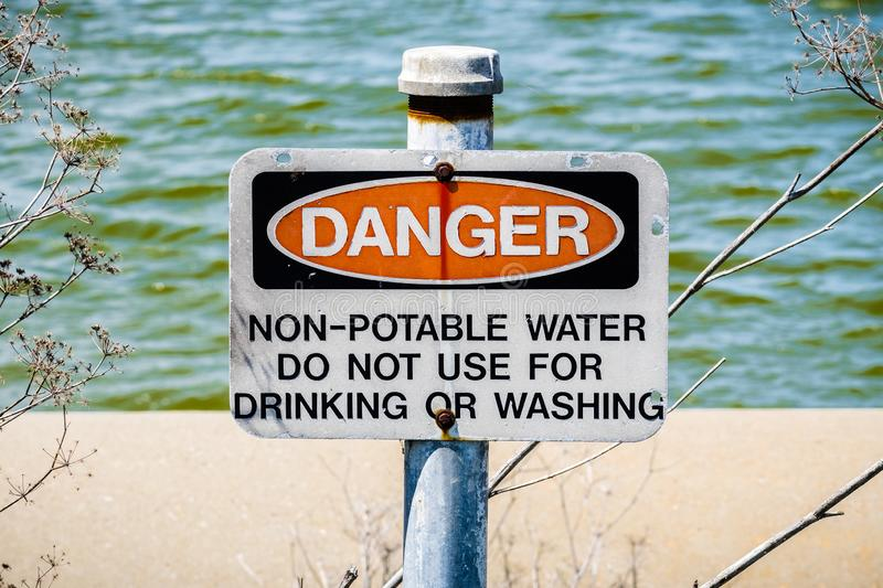 Danger Non-potable water sign. `Danger Non-potable water ` sign posted on the shorelines of south San Francisco bay area, California royalty free stock images