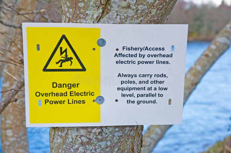Danger notice for fishermen. An image of a warning notice fixed to a tree beside a river reminding fishermen of overhead electric power cables and the danger if stock photo