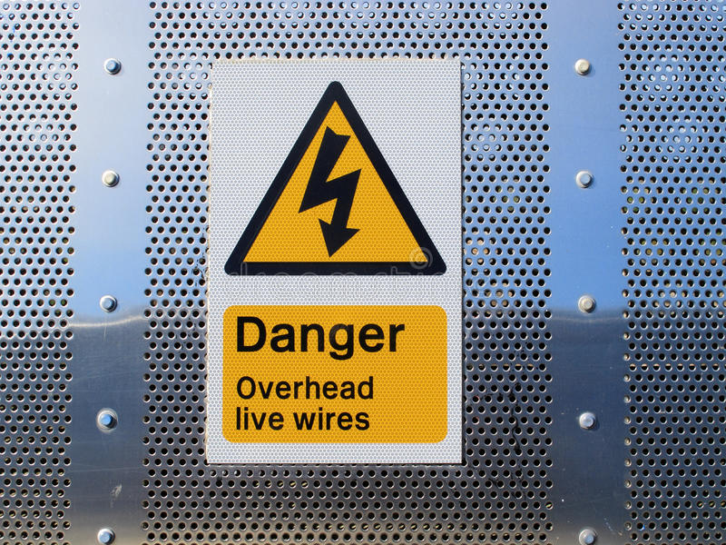 Danger overhead wires sign. A sign showing danger overhead wires complete with a black on yellow electrical danger flash stock photography