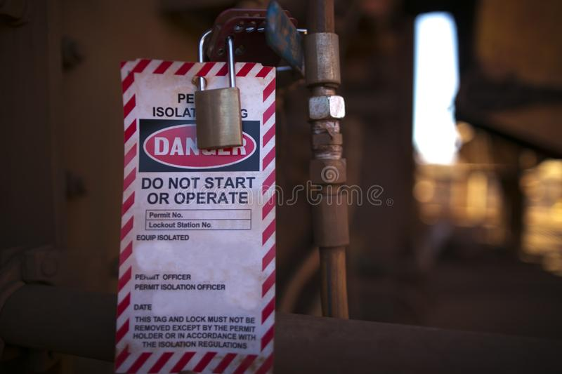 Danger permit isolation tag do not start or operate and locking to control life plant starting up. Protection the risk of hazard at construction mine site royalty free stock photography