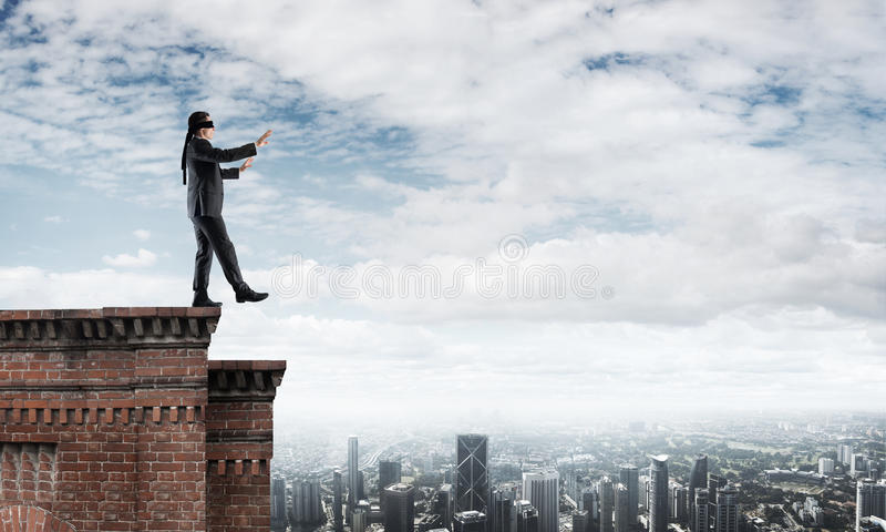 Danger and risk concept with businessman making step from edge. Businessman with blindfolder on eyes walking on building top royalty free stock photos