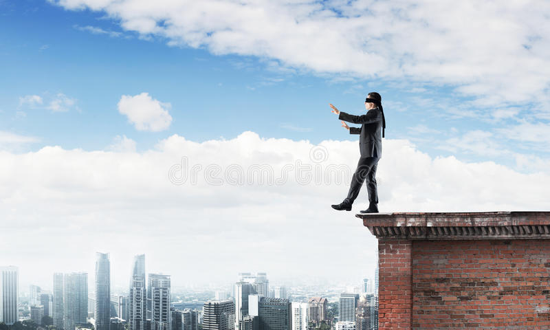 Danger and risk concept with businessman making step from edge. Businessman with blindfolder on eyes walking on building top stock photos