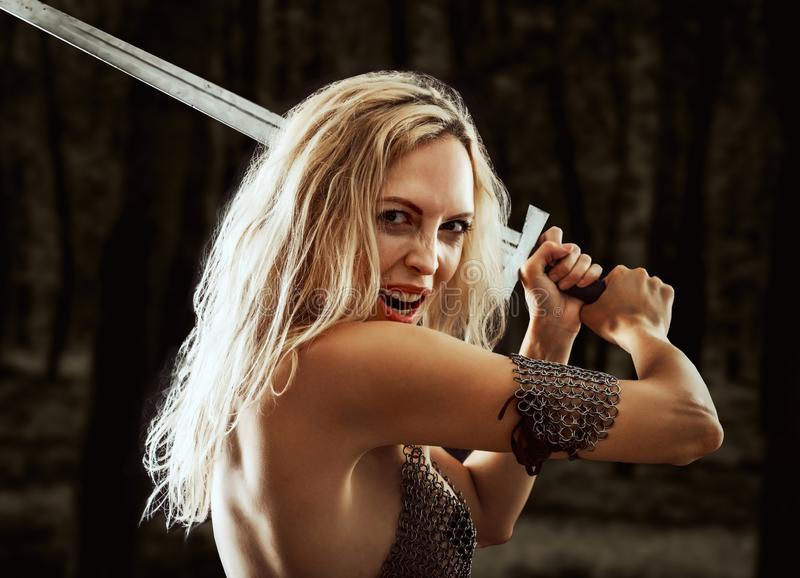Danger warrior viking girl with sword attack. Beautiful warrior viking girl with a sword in hands attack and screaming on dark forest background royalty free stock photos