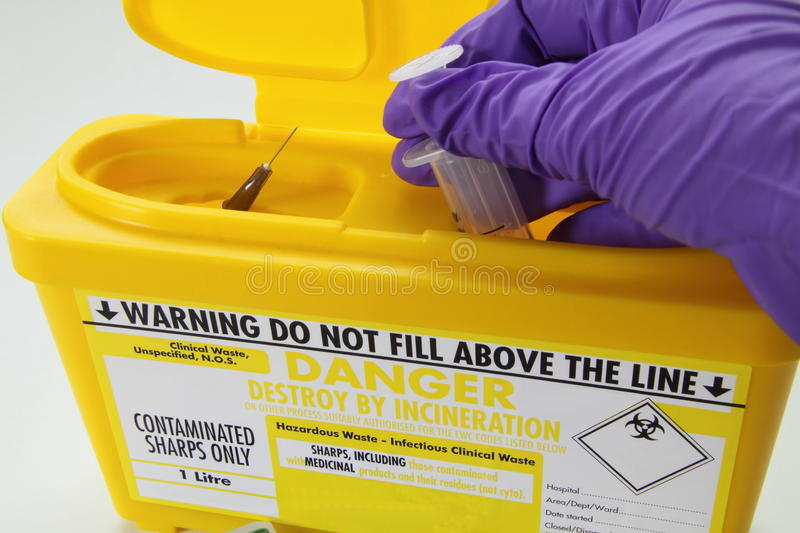 Danger sharp needle hazard. Hand in a surgical glove putting a syringe in a needle box used in hospital for the disposal of contaminated sharps stock images
