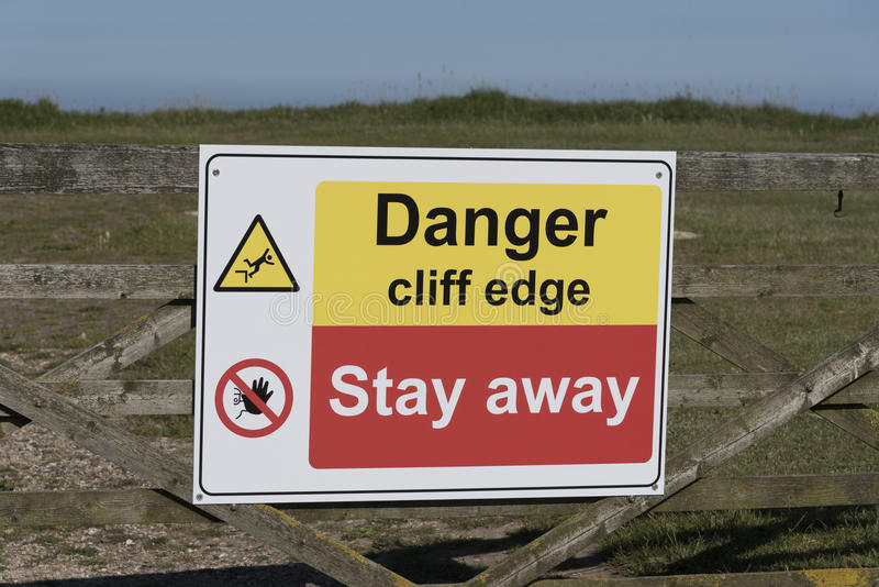Danger sign on a cliff edge. Danger signs on the cliff edge at Peveril Point in Swanage Bay Dorest England UK royalty free stock photo