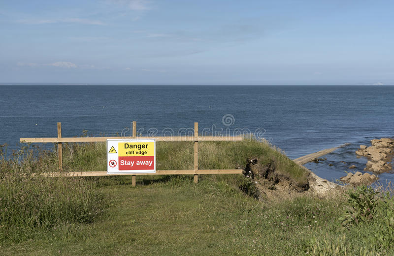 Danger sign on a cliff edge. Danger signs on the cliff edge at Peveril Point in Swanage Bay Dorest England UK royalty free stock photos