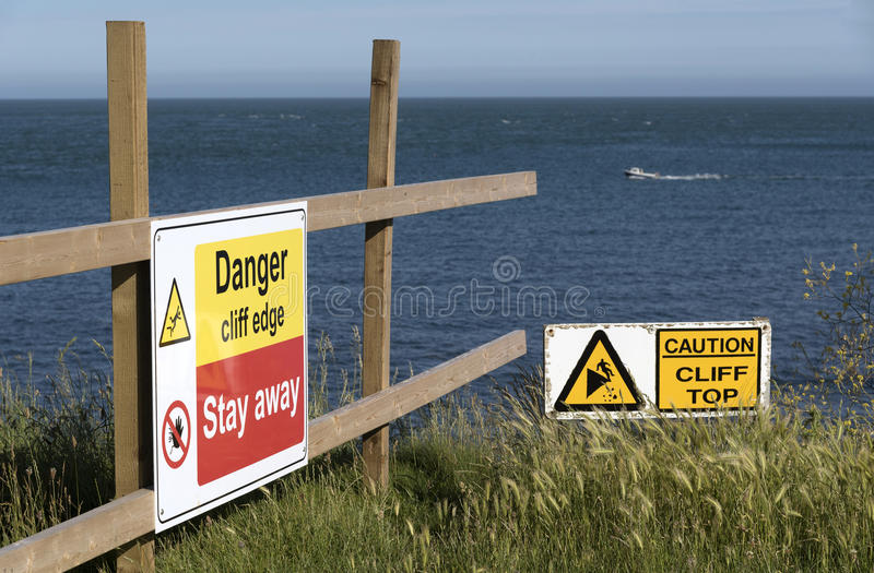 Danger sign on a cliff edge. Danger signs on the cliff edge at Peveril Point in Swanage Bay Dorest England UK stock photography