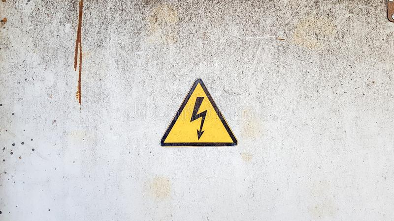 Danger sign of high voltage electricity. Yellow triangular sign with a lightning in the center. This warning is written on an old royalty free stock images