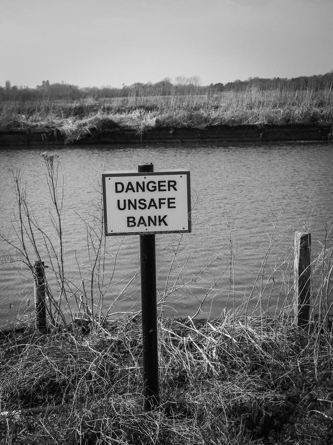 Danger sign unsafe bank. Danger sign next to river unsafe bank riverbank Norfolk Broads banking royalty free stock photography