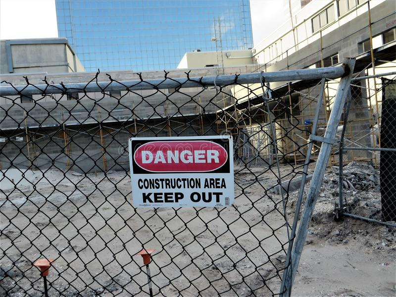 Danger sign at urban construction site, Tampa, Florida. Danger Construction Area KEEP OUT sign on chain link fence with black tarp at downtown construction site royalty free stock photos