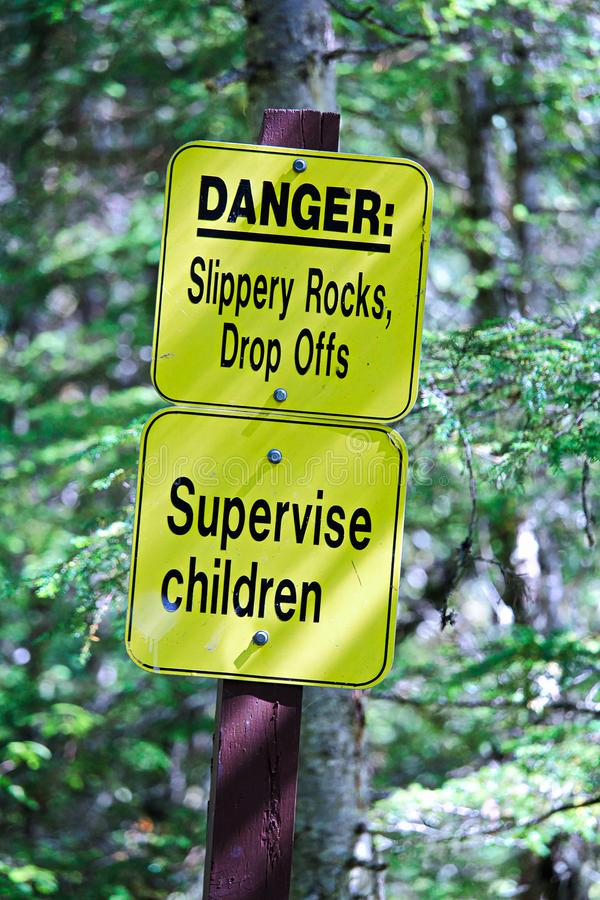 Danger slippery rocks, drop offs and supervise children sign stock image