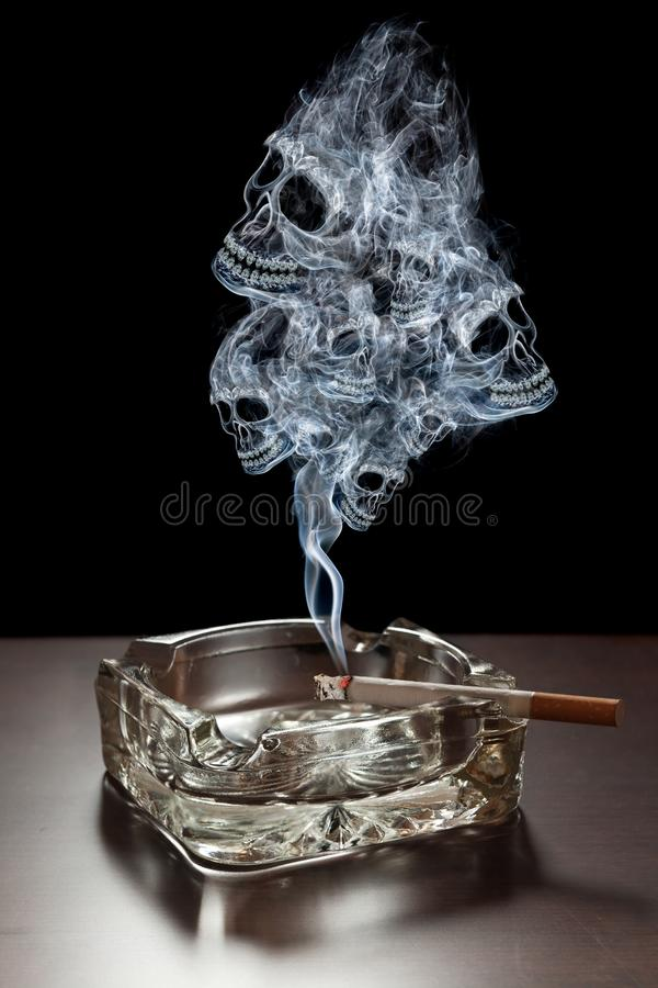 Danger of smoking. Many smoke skulls rising from a cigarette stock photography