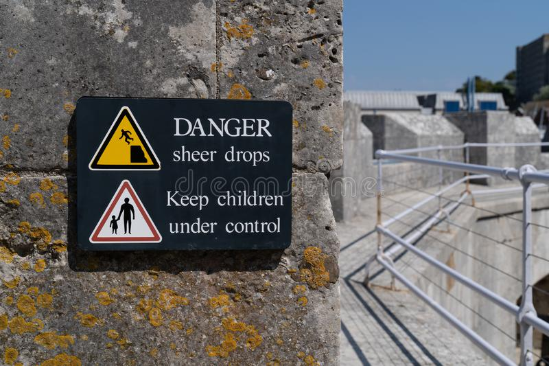 Danger sudden drop sign yellow warning triangle with symbol of man falling from a cliff edge and keep children under control sign. On rampage royalty free stock photo