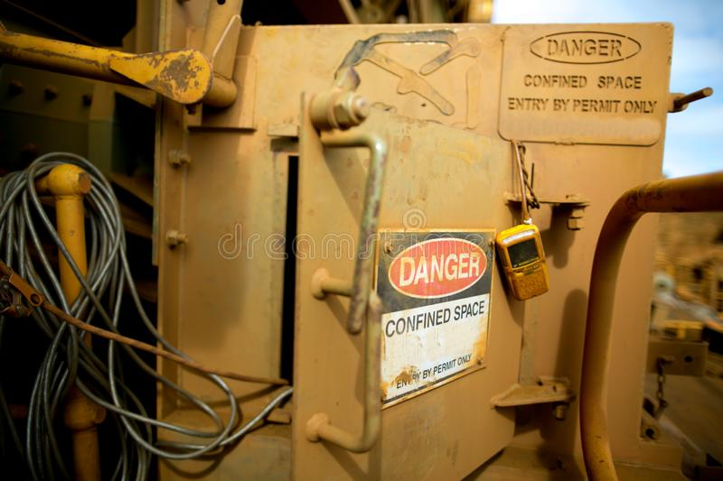 Danger tag confined space sign entry  authorised personnel by permit only with gas test detector atmosphere hanging on the door. Fame at construction mine site stock photos