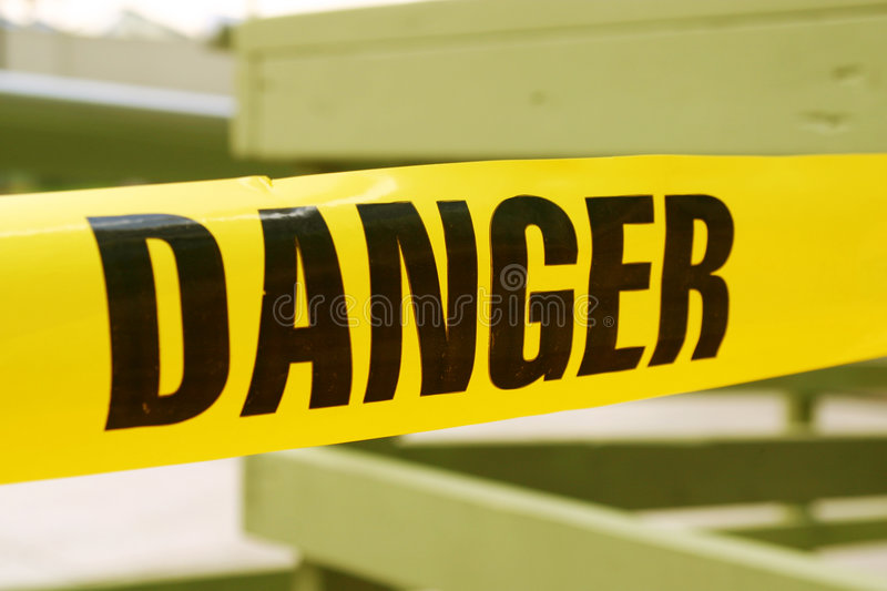 Danger tape. Stretched out with wooden fence background royalty free stock photography