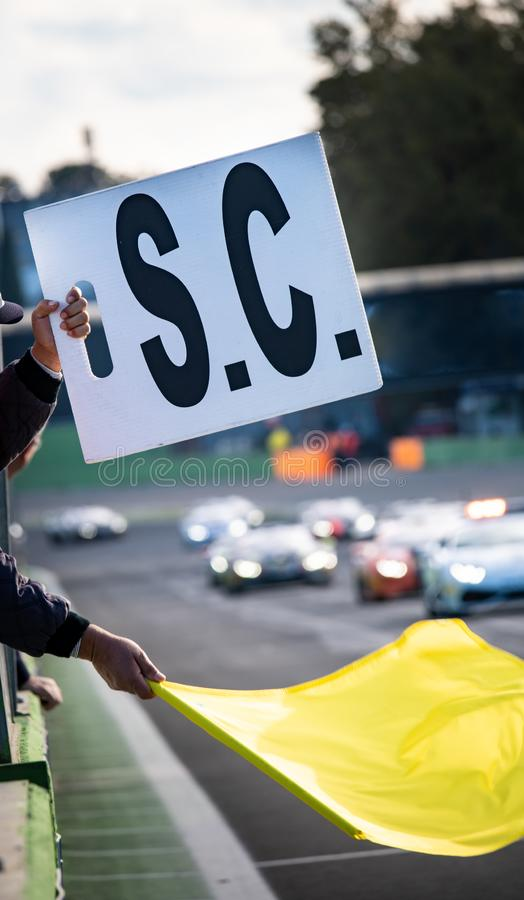 Danger on track warning sign during car racing. Danger on track warning waved yellow flag and safety car sign exposed during car racing, selective focus stock images