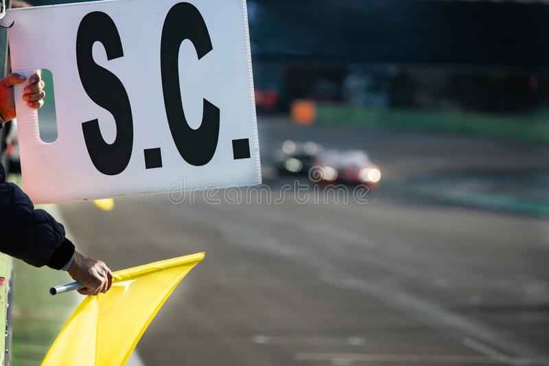 Danger on track warning sign during car racing. Danger on track warning waved yellow flag and safety car sign exposed during car racing, selective focus stock photo