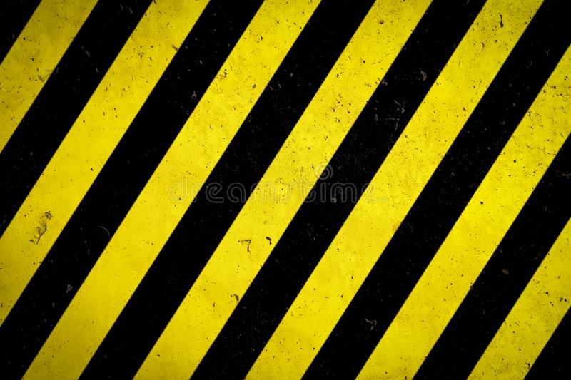 Danger zone: Warning sign yellow and black stripes painted over concrete wall coarse facade with holes and imperfections texture stock illustration