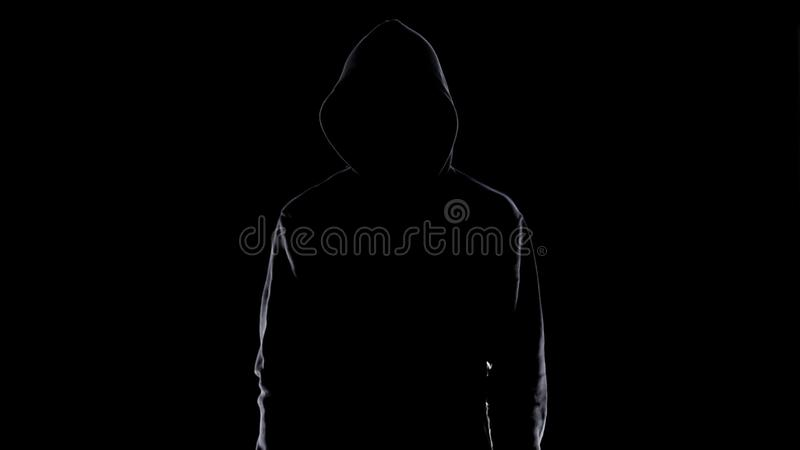 Dangerous anonymous male in night darkness, scary terrorist preparing for crime stock photo
