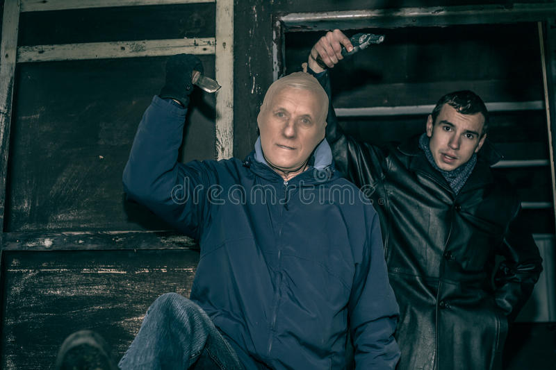 Dangerous armed men. Two dangerous armed men pointing with weapons and standing in old dark cabin royalty free stock photo