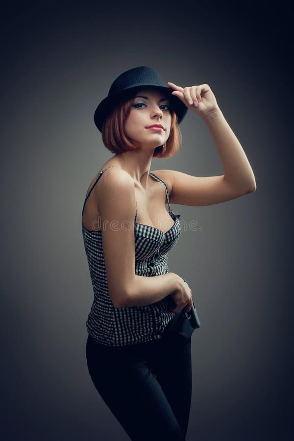 Dangerous and beautiful criminal girl with gun stock photography