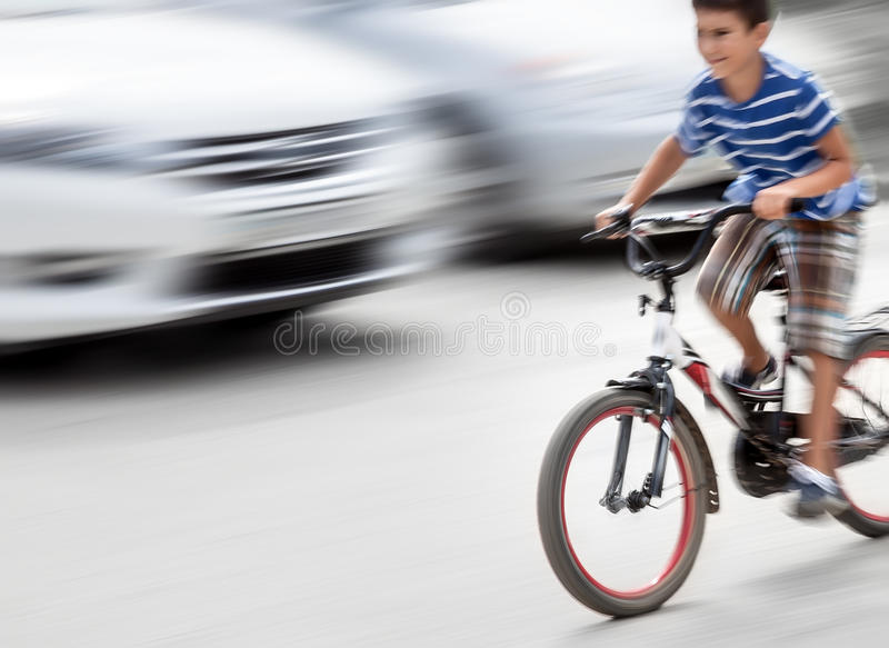 Dangerous city traffic situation with a boy on bicycle. And cars in motion blur. Intentional motion blur royalty free stock photography