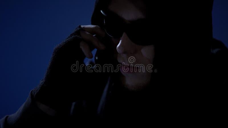 Dangerous criminal threatening victim by phone, demanding money via blackmail stock photos