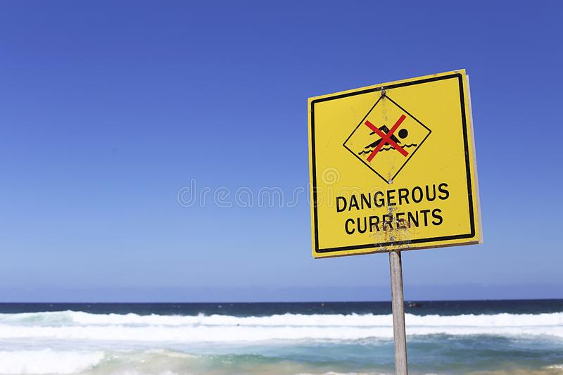 Dangerous currents sign. On the beach at sunny day stock photo