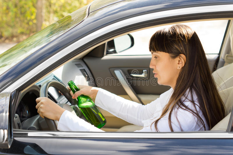Dangerous driving. With a drunk and inebriated female driver staring blearily at her steering wheel as she drives along holding a bottle of booze in her hand stock photos