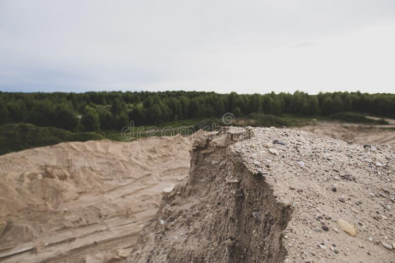 Dangerous edge of the sand quarry and steep cliff down. Quarrying and mining of building material. View from the top. Dangerous edge of the sand quarry and royalty free stock photos