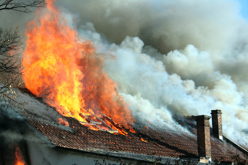 Dangerous fire. Roof of an old building caught on fire stock photos