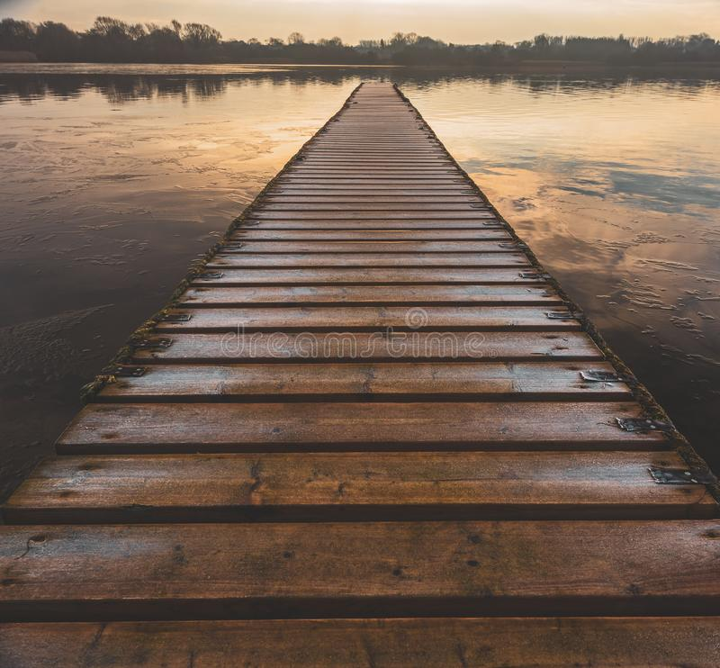 A dangerous frozen wooden walkway leads out into the middle of a lake royalty free stock photo
