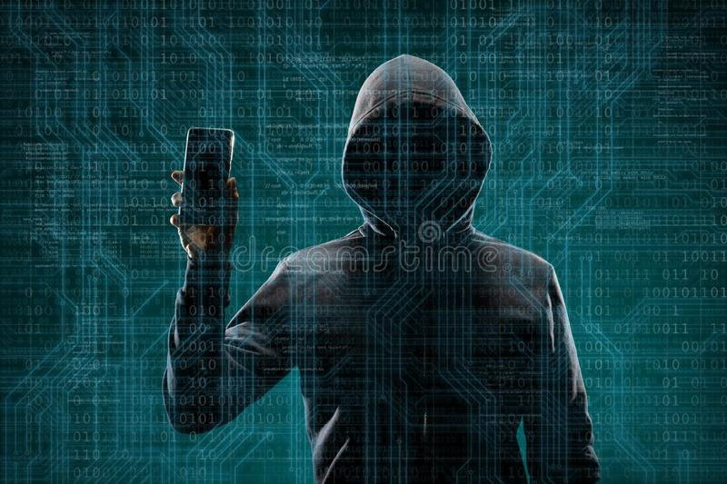 Dangerous hacker with a smartphone gadget over digital background with binary code. Obscured dark face in mask and hood. Data thief, internet attack, darknet royalty free stock photos