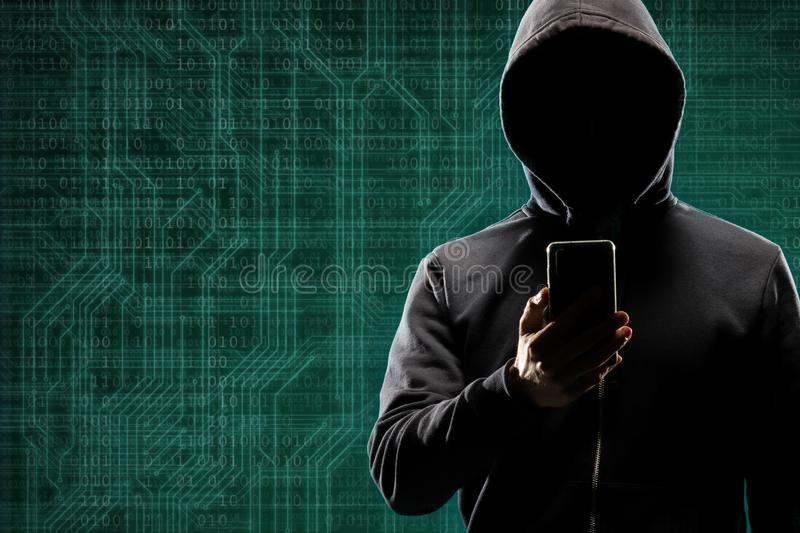 Dangerous hacker with a smartphone gadget over digital background with binary code. Obscured dark face in mask and hood. Data thief, internet attack, darknet royalty free stock image