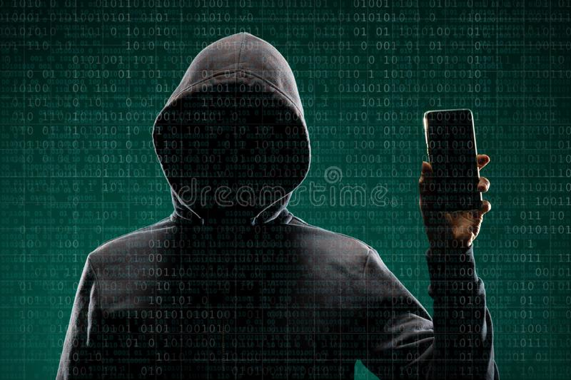 Dangerous hacker with a smartphone gadget over digital background with binary code. Obscured dark face in mask and hood. Data thief, internet attack, darknet stock image