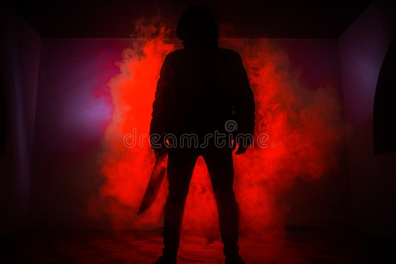 A dangerous hooded man standing in the dark and holding a knife. Face can not be seen. Committing a crime concept. Selective focus royalty free stock images