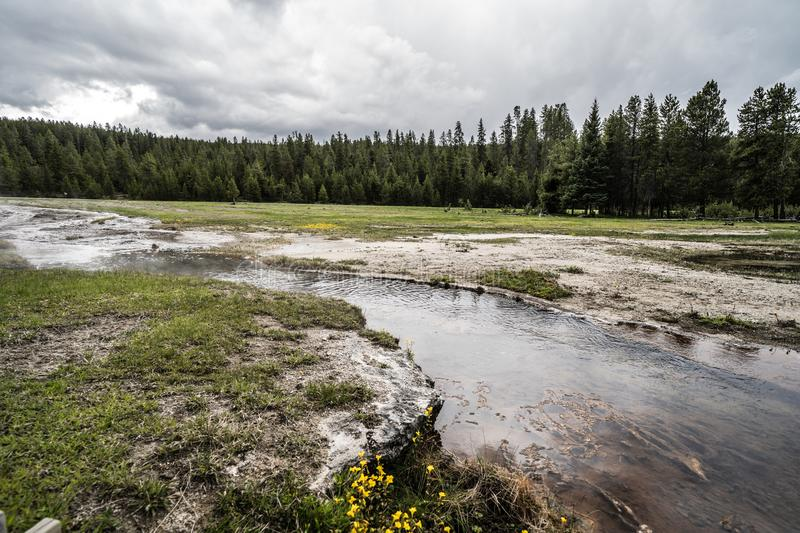 Wide angle view of a hot spring thermal river of water in Yellowstone National Park. Dangerous hot spring hot water flows through the Firehole Lake drive area of stock photo