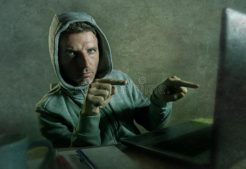 Dangerous looking hacker man in hoodie hacking internet computer system pointing his eyes warning about his ability to break passw. Dangerous looking hacker man royalty free stock image