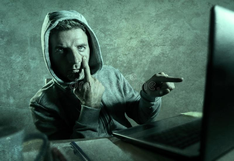 Dangerous looking hacker man in hoodie hacking internet computer system pointing his eyes warning about his ability to break passw. Dangerous looking hacker man stock image