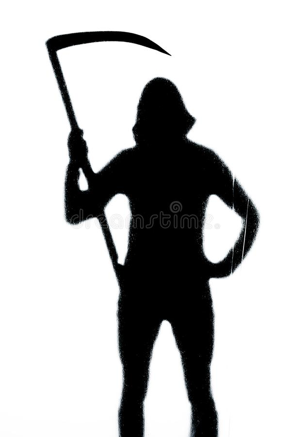 Dangerous man behind frosted glass with a scythe in his hand. Halloween. Black and white image stock image