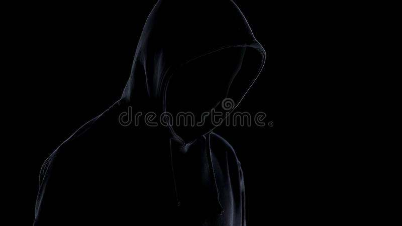 Dangerous maniac in mask and hoodie standing against black background, crime royalty free stock image